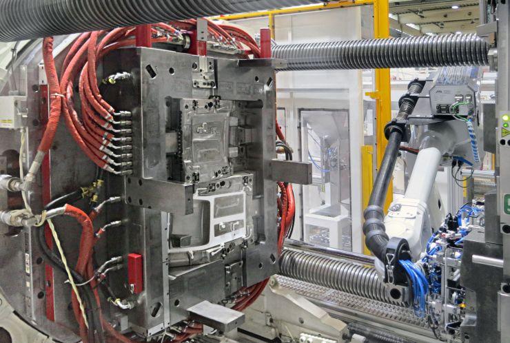 Die »duo 700« von Engel ist für die Dreikomponentenfertigung der Mittelkonsolen mit einem Drehteller ausgerüstet: Ein Knickarmroboter entnimmt die Spritzgießteile. Bild: Engel